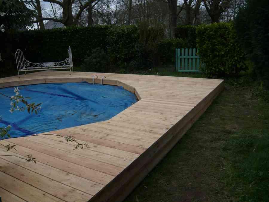dans un cadre arboré, cette terrasse bois met en valeur cette piscine